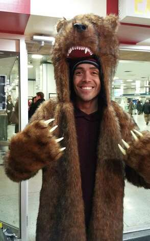 """Dressed in grizzly bear garb, Cicero Goncalves looks to be well prepared for snowy weather as he waits in New York's Penn Station for a train to Vermont, Sunday, Jan. 26, 2015.  Goncalves was headed north for some snowboarding, and was traveling by train because he expected the flight he had hoped to take would be canceled due to a storm that could dump 2 to 3 feet of snow from  starting Monday. Goncalves, a 34-year-old flight attendant from Queens, counted himself and his travel partner as lucky. """"We'll get there before it snows, and we're coming back when the storm is over, on Thursday,"""" he said. A blizzard warning was issued for New York and Boston, and the National Weather Service said the massive storm would bring heavy snow and powerful winds starting Monday and into Tuesday. (AP Photo/Verena Dobnik) ORG XMIT: NYR101 Photo: Verena Dobnik / AP"""