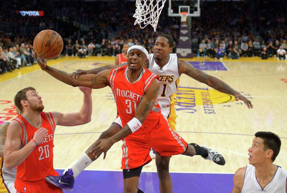 Rockets guard Jason Terry, second from left, is fouled by Lakers forward Ed Davis as he drives to the basket. Terry had 11 points in nearly 21 minutes off the bench Sunday. Photo: Mark J. Terrill, STF / AP