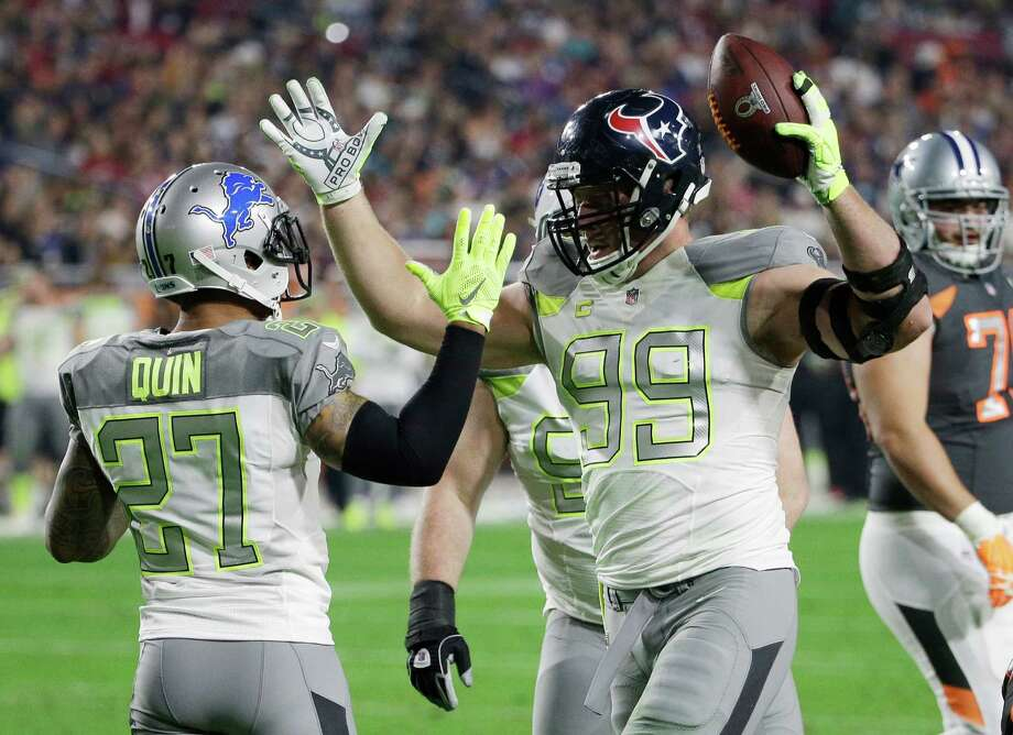 J.J. Watt (99) is congratulated by former Texans teammate Glover Quin after Watt's goal-line interception in the first half Sunday night. Photo: David J. Phillip, STF / AP
