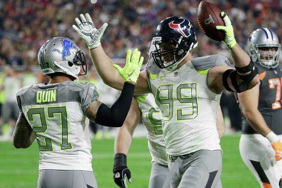 J.J. Watt (99) is congratulated by former Texans teammate Glover Quin after Watt's goal-line interception in the first half Sunday night.