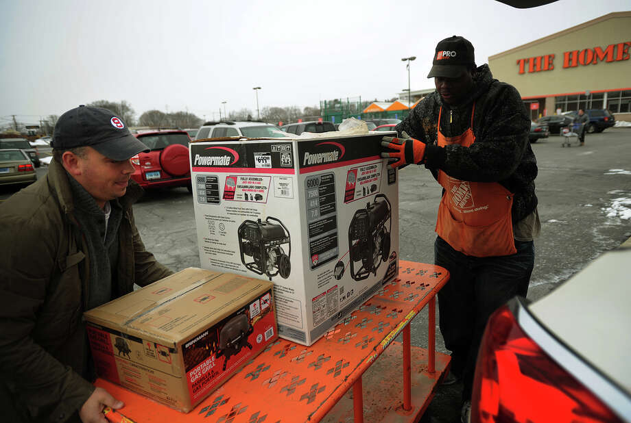 With a one week old baby at home, Chris Howe, right, of Stratford, loads a generator into his car with the help of Home Depot employee David Perry, of Stratford, in preparation for the coming blizzard in Stratford, Conn. on Monday, January 26, 2015. Photo: Brian A. Pounds / Connecticut Post