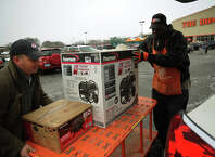 With a one week old baby at home, Chris Howe, right, of Stratford, loads a generator into his car with the help of Home Depot employee David Perry, of Stratford, in preparation for the coming blizzard in Stratford, Conn. on Monday, January 26, 2015.