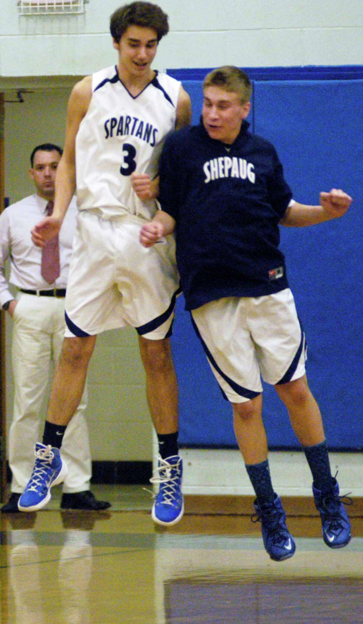Rob McCarthy, left, of the Spartans is greeted in mid-flight by teammate Mike Taylor during pre-game introductions before Shepaug Valley High School boys' basketball's 62-53 victory over Housatonic Valley Regional, Jan. 23, 2015 in Washington. Looking on is Shepaug Valley School security guard Andrew St. Jean.