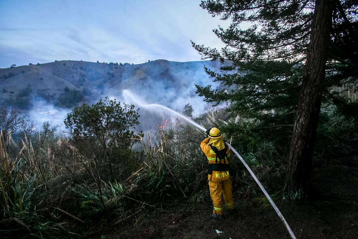 Firefighters battle a 6-alarm brush fire that began on Fassler Avenue and spread to Rockaway Beach Avenue, Monday, Jan. 26, 2015, in Pacifica, Calif.