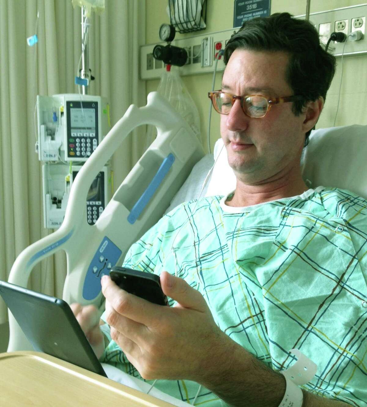 Vigilant about his town's well being even while bed-ridden the morning after undergoing an emergency appendectomy at New Milford Hospital, First Selectman Clay Cope employs his iPad and iPhone Monday to coordinate Sherman's preparedness for the snowstorm about to arrive. Jan. 26, 2015