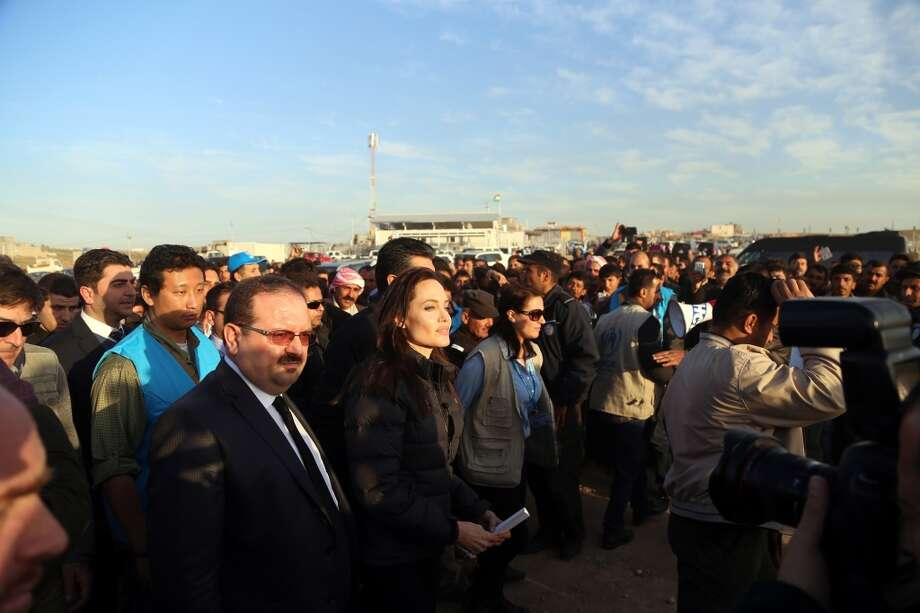 United Nations High Commissioner for Refugees (UNHCR) Special Envoy and famous actress Angelina Jolie (C) walks with the crowd during his visit at Hanke Refugee camp, built by UN for the Ezidi Refugees, fled from attacks of the Islamic State of Iraq and the Levant (ISIL), in 10 km west of Dohuk, Iraq on January 25, 2015. Photo: Anadolu Agency, Getty