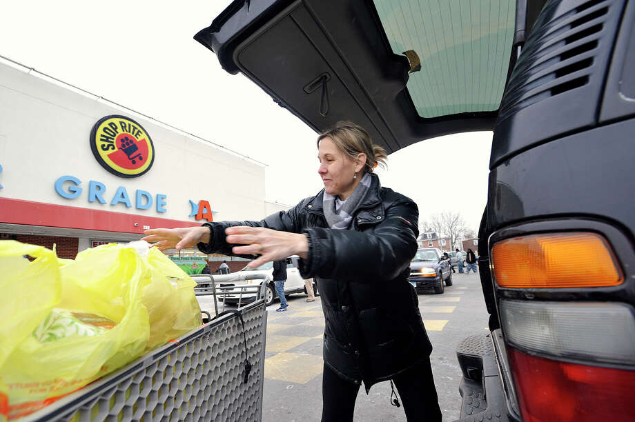 Chris Smith, of Stamford, loads up the back of her vehicle at the Shop Rite on Shippan Avenue in Stamford, Conn., on Monday, Jan. 26, 2015. Chris says that she's not worried about the impending snow storm. Photo: Jason Rearick / Stamford Advocate