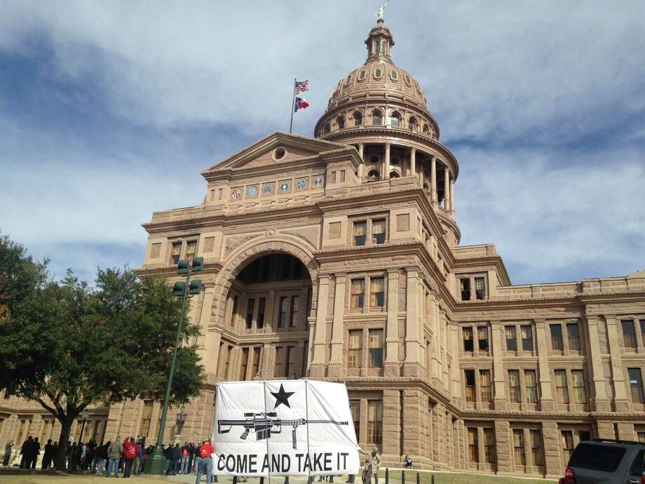 "A giant ""Come and Take It"" flag is posted in front of the state Capitol in Austin as roughly 75 open carry activists gather outside on Monday, Jan. 26, 2015. The demonstrators support Rep. Jonathan Stickland's House Bill 195, which would legalize unlicensed open carry of handguns. Photo: Lauren McGaughy/Houston Chronicle"