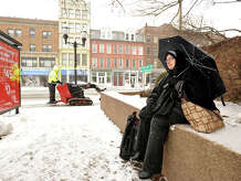 Stamford resident Amina Ali waits for her bus in downtown Stamford, Conn., while on her way home from the hospital on Monday, Jan. 26, 2015.
