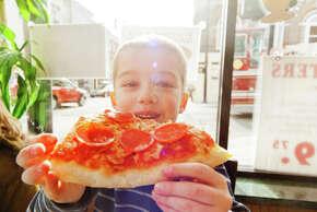 New York Portrait of boy eating slice of pizza