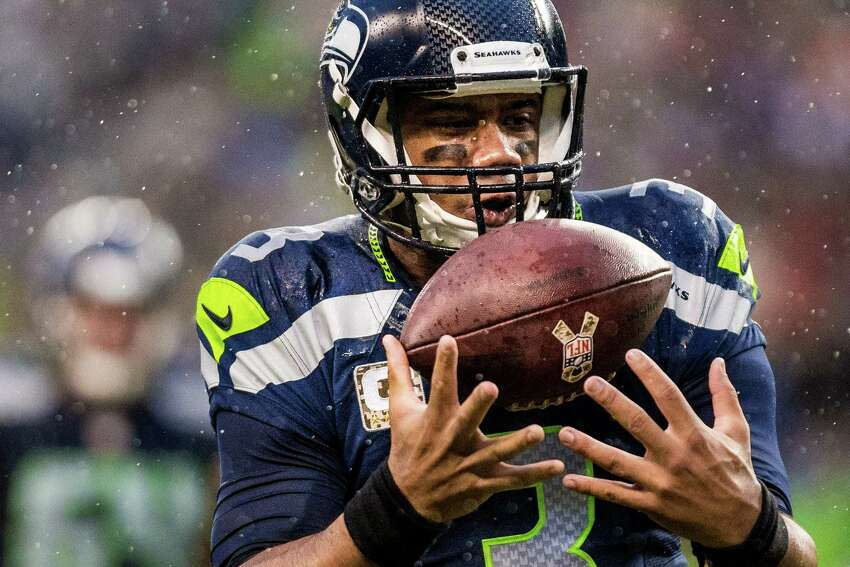 Seahawks quarterback Russell Wilson makes an on-the-go recovery during a run downfield against the Giants on Sunday, November 9, 2014, at CenturyLink Field. The Seahawks beat the Giants 38-17.