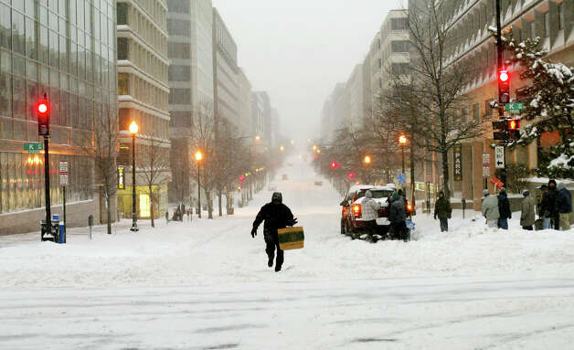 FILE - In this Feb. 16, 2003 file photo, a pedestrian makes his way up snow-covered 20th Street NW at K Street NW in the heart of the Washington business district as the most extreme winter weather in recent years hits the nation's capital.  This storm on Presidents' Day weekend paralyzed an swath of the Northeast from Washington to Boston, producing the latter city's heaviest snowfall on record, a whopping 27.6 inches. Photo: J. SCOTT APPLEWHITE, AP / AP