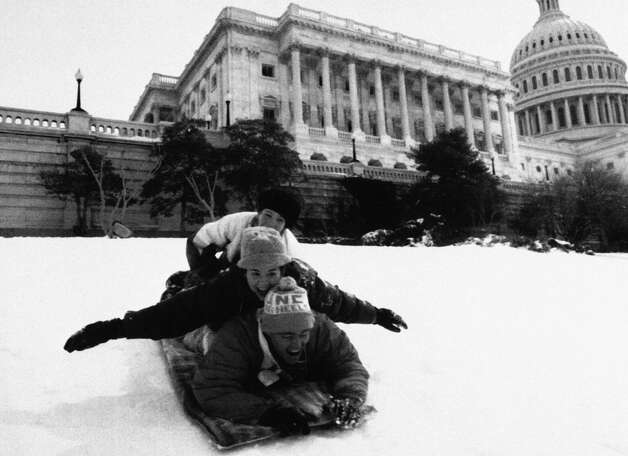 """FILE - In this March 14, 1993 file photo, cousins Allen, bottom, and Lauren Haywood, middle, and Aubrey Parsons, all from Washington, take advantage of the snowy hill in front of the Capitol in Washington. Dubbed the """"Storm of the Century,"""" the intense 1993 storm produced tremendous amounts of snow from Tennessee to the Canadian border, with many locations breaking snowfall records. Photo: Mark Wilson, AP / AP"""
