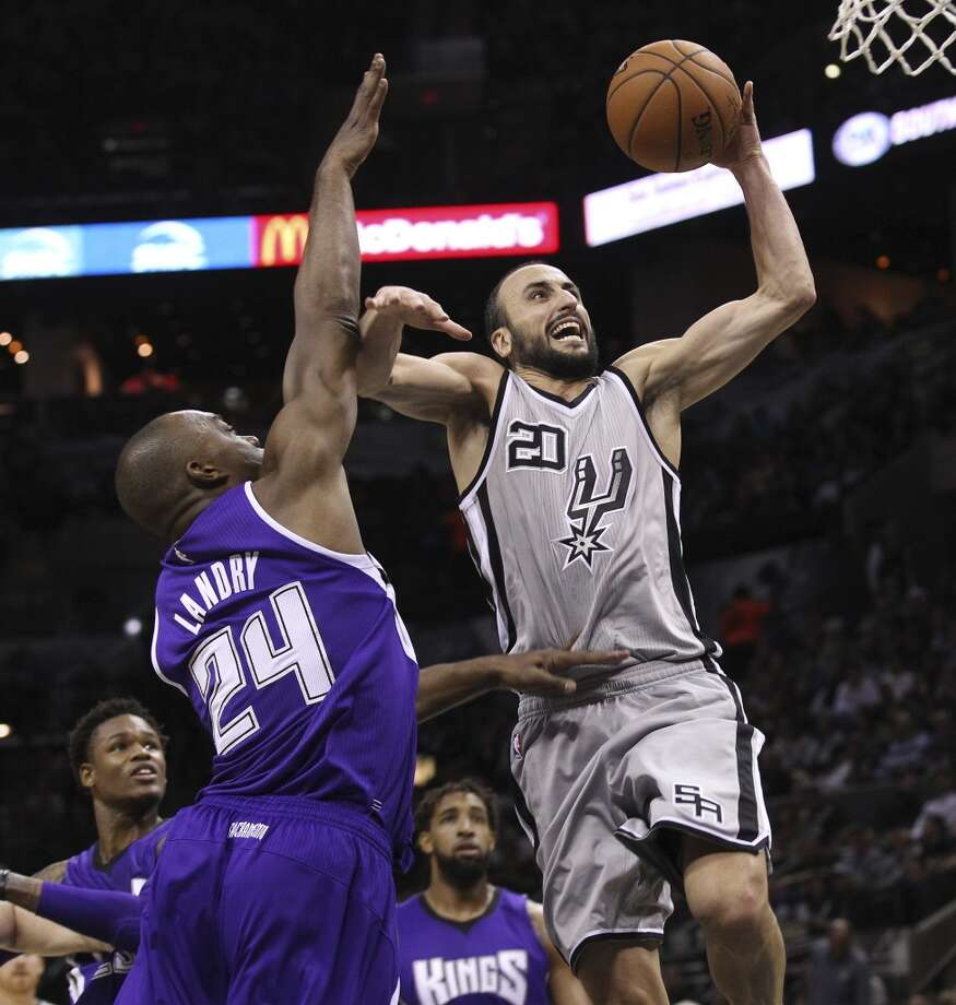 Spurs' Manu Ginobili (20) goes strong to the basket against the Sacramento Kings' Carl Landry (24) at the AT&T Center on Friday, Nov. 28, 2014. Spurs defeat the Kings 112-104. (Kin Man Hui/San Antonio Express-News) Photo: San Antonio Express-News