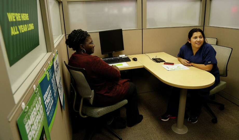 H&R Block office manager Dianne Butler, left, sits with her client Claudia Chacon as she talks about her ability to avoid paying a penalty for not buying insurance last year while doing her taxes at H&R Block at 9474 Hammerly Blvd. Wednesday, Jan. 21, 2015, in Houston.  This is the first tax filing season for those consumers who bought insurance in the health insurance marketplace.  They are going to have to complete extra paperwork to determine whether the premium subsidies they received were for the correct amount.  ( Karen Warren / Houston Chronicle  ) Photo: Karen Warren, Staff / © 2015 Houston Chronicle