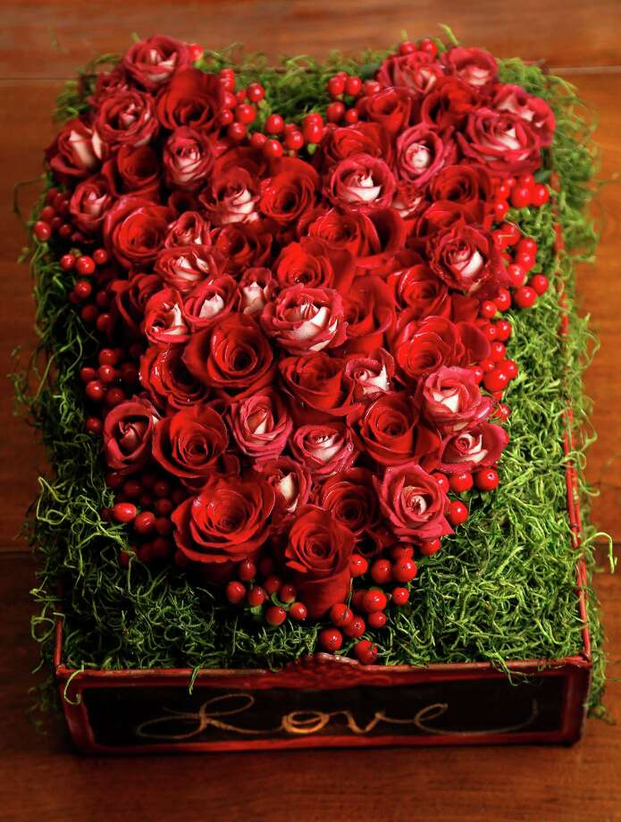 Floral designer Lisa Wright's valentine arrangement varies from the norm - a wire crate with moss topped with red roses. Photo: Karen Warren, Staff / © 2015 Houston Chronicle