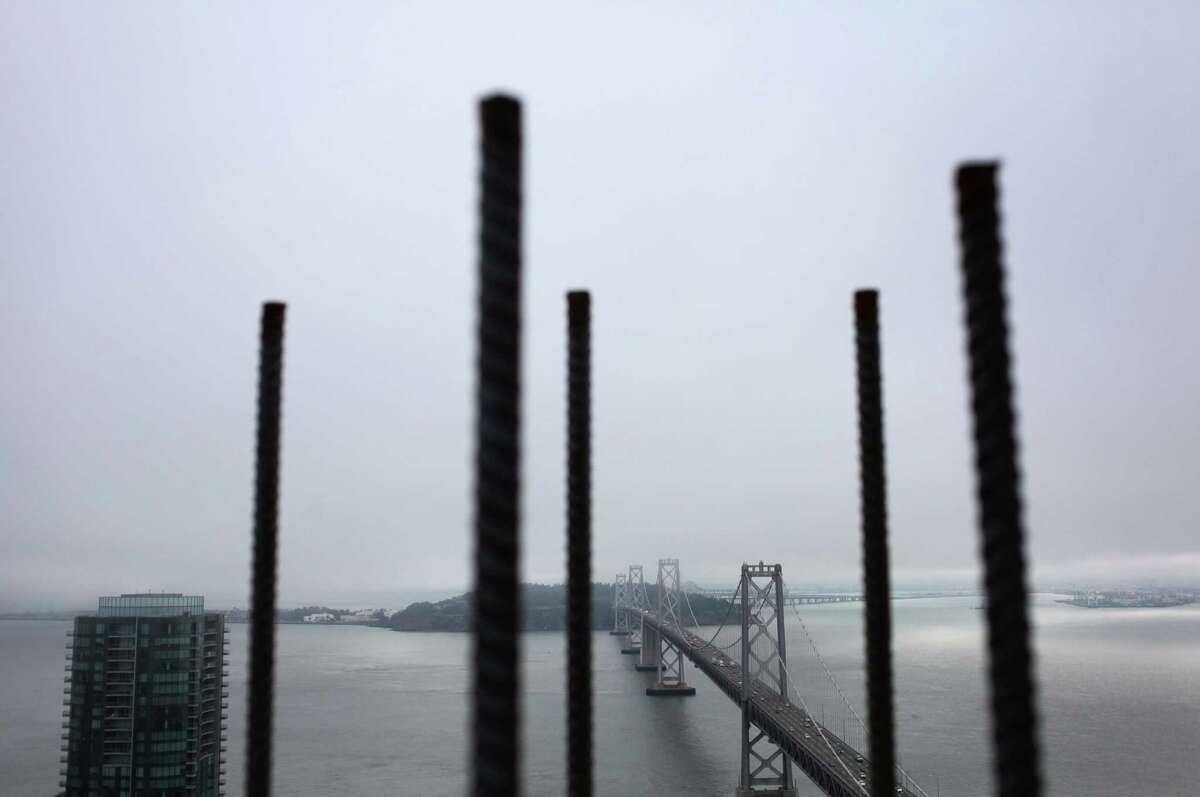 Exposed pieces of rebar frame the Bay Bridge as seen from atop One Rincon Hill Phase Two in San Francisco in 2013.