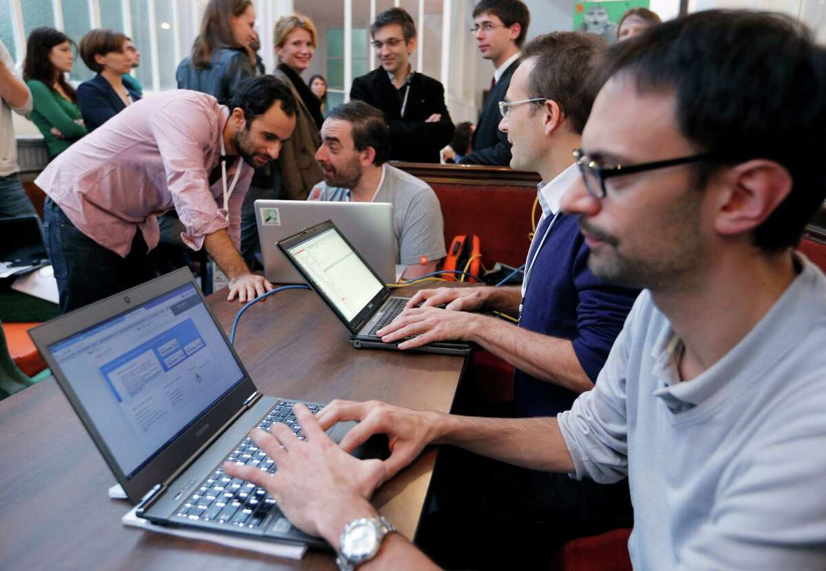 Software developers work on laptops during the 'Hackathon Dataculture', a one-or two-day hack event dedicated to open cultural data on October 25, 2013 in Paris. The hackathons are informal workshops bringing together software developers during one or two days, to build projects and prototypes and develop innovative applications for open cultural data. AFP PHOTO / FRANCOIS GUILLOT