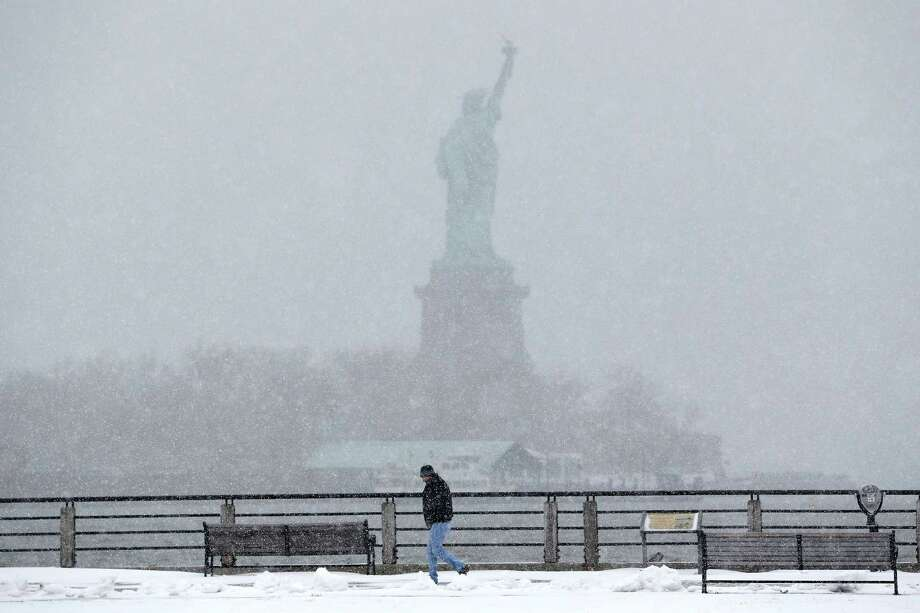 A man strolls on a walking path at Liberty State Park, with the Statue of Liberty in the distance, in Jersey City, N.J., a day ahead of Tuesday's predicted big blizzard. More than 35 million people in the Northeast were hunkering down. Photo: Julio Cortez, STF / AP