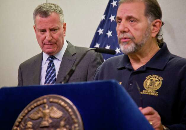 New York City Mayor Bill de Blasio, left, listens as Joseph Esposito, commissioner of the New York City Office of Emergency Management (OEM), speaks a during press conference at OEM, Monday, Jan. 26, 2015, in New York.  De Blasio says streets will be closed to all but emergency vehicles starting at 11 p.m. Monday ahead of the expected 18 to 24 inches of snow.  (AP Photo/Bebeto Matthews) ORG XMIT: NYBM103 Photo: Bebeto Matthews / AP