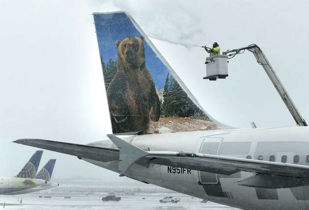 A crewmember de-ices a Frontier Airlines plane at LaGuardia Airport in New York, Monday, Jan. 26, 2015. More than 5,000 flights in and out of East Coast airports have been canceled as a major snowstorm packing up to three feet of snow barrels down on the region. (AP Photo/Seth Wenig) ORG XMIT: NYSW109 Photo: Seth Wenig / AP