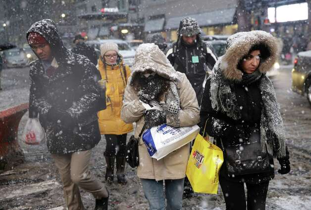 Pedestrians make their way through heavy snow in midtown Manhattan in New York, Monday, Jan. 26, 2015. The Philadelphia-to-Boston corridor of more than 35 million people began shutting down as a monster storm, that could unload a paralyzing 1 to 3 feet of snow, moved through the northeast. (AP Photo/Seth Wenig) ORG XMIT: NYSW123 Photo: Seth Wenig / AP