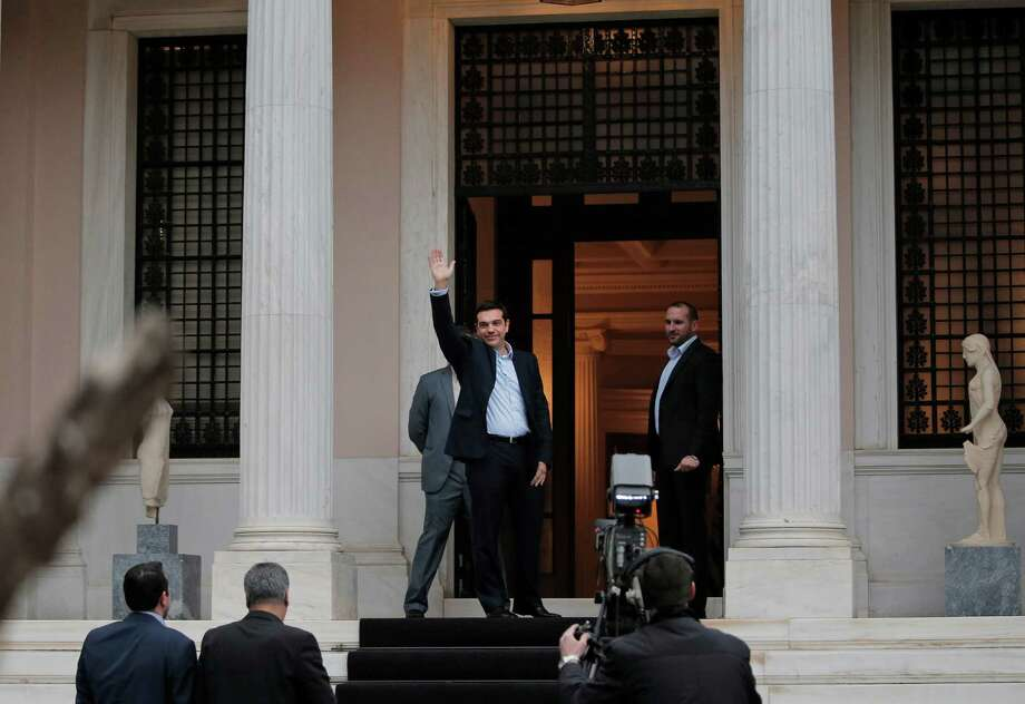 Greece's Prime Minister Alexis Tsipras waves to the members of media as he arrives at Maximos Mansion, the Greek Prime Minister's official residence in Athens, Monday, Jan. 26, 2015. Radical left leader Alexis Tsipras has been sworn in as Greece's new prime minister, becoming the youngest man to hold the post in 150 years. (AP Photo/Lefteris Pitarakis) Photo: Lefteris Pitarakis, STF / AP