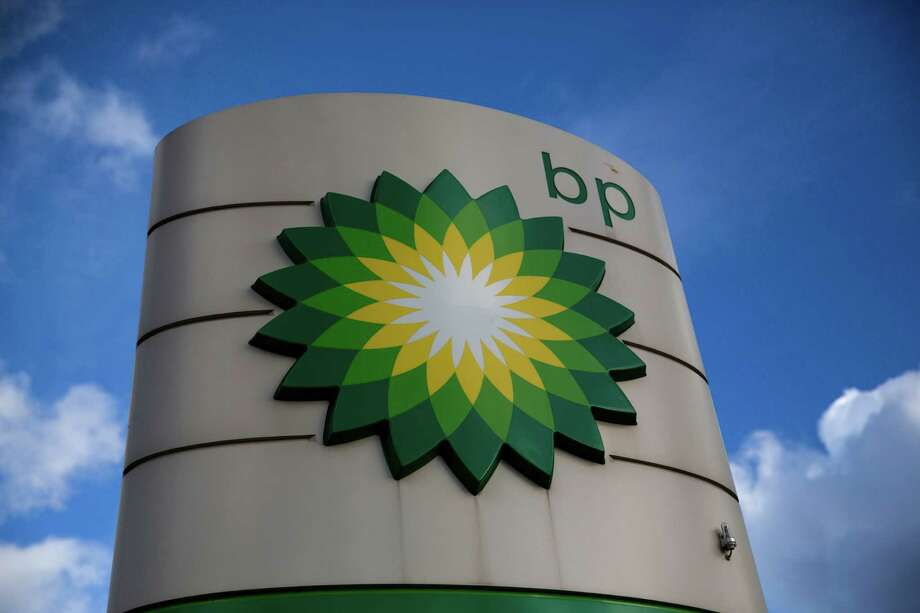 British oil company BP, which displays its logo at this gasoline staion in Bletchley, England,  has frozen most employee pay levels in response to plunging oil prices. BP has its U.S. headquarters in Houston, where it employs more than 7,200.  (AP Photo/Matt Dunham) Photo: Matt Dunham, STF / AP