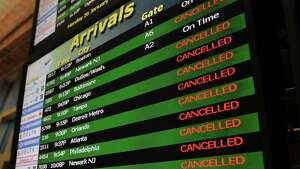 The monitor showing arrival flights at the Albany International Airport is full of cancellations on Monday, Jan. 26, 2015, in Albany, N.Y.  (Paul B