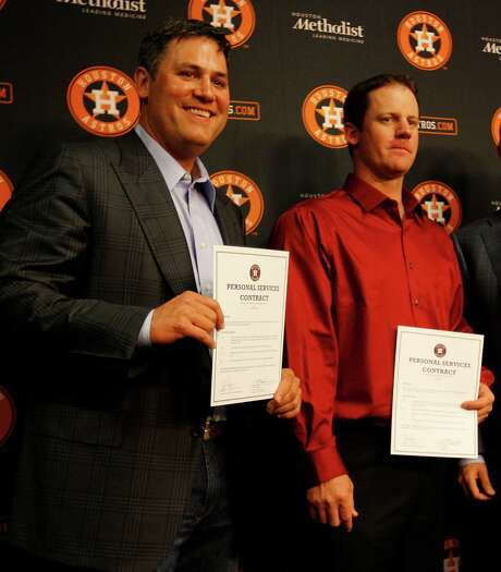 Lance Berkman and Roy Oswalt hold up their one-day contracts with the Houston Astros during a press conference before the start of a baseball game at Minute Maid Park, Saturday, April 5, 2014, in Houston. ( Karen Warren / Houston Chronicle  ) Photo: Karen Warren, Staff / © 2014 Houston Chronicle