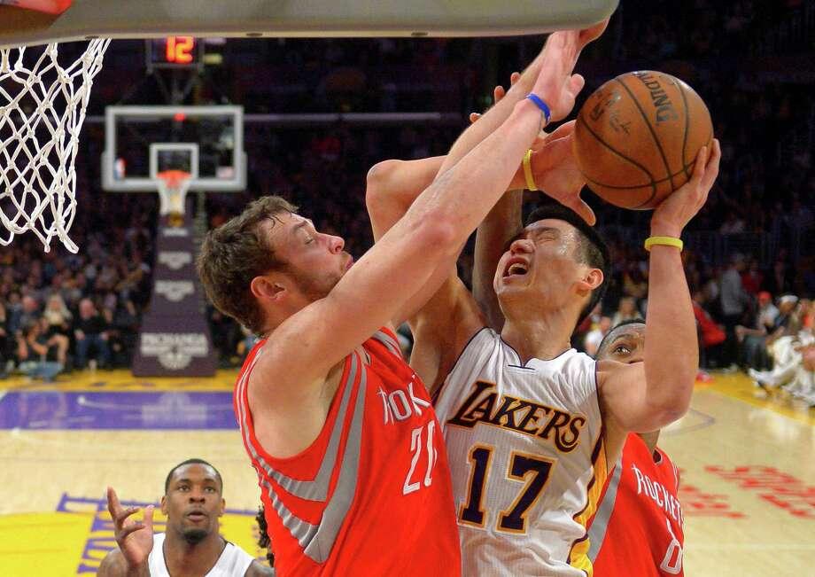 The Rockets' Donatas Motiejunas smothers Lakers guard Jeremy Lin on Sunday. Photo: Mark J. Terrill, Associated Press / AP