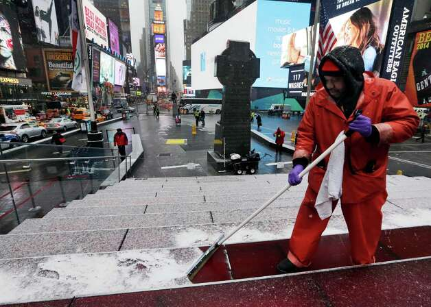 """Francisco Mathurine, of the Times Square Alliance, clears snow from the steps in Father Duffy Square in New York, Monday, Jan. 26, 2015. Officials cautioned Northeast residents to not be misled by a relatively smooth Monday morning commute, and pressed their cautions to prepare for a """"crippling and potentially historic"""" storm that could bury communities from northern New Jersey to southern Maine in up to 2 feet of snow starting later in the day. (AP Photo/Richard Drew) ORG XMIT: NYRD101 Photo: Richard Drew / AP"""