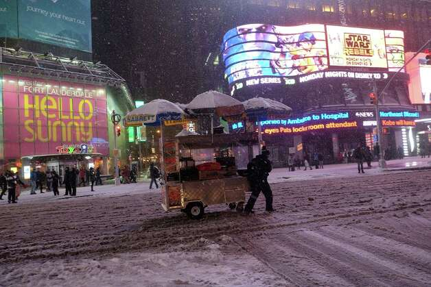 """A vendor steers his cart through a street in New York's Times Square during a snow storm on January 26, 2015. A winter storm pounded the northeastern United US on January 26 hitting tens of millions of people and forcing the rare cancelation of Broadway shows in an """"historic"""" New York blizzard. Winter Storm Juno is expected to dump up to three feet (around a meter) of snow in parts of the northeast, with the worst affected areas likely to be New England, particularly Connecticut and Massachusetts. More than 6,560 flights on Monday and Tuesday were cancelled, the New York city transit system was to shut at 11pm and road travel made a criminal offense in 13 counties of New York state. AFP PHOTO/JEWEL SAMADJEWEL SAMAD/AFP/Getty Images ORG XMIT: 34360203 Photo: JEWEL SAMAD / AFP"""