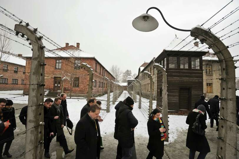 Visitors walk by barbed wire fences at the Auschwitz Nazi death camp in Oswiecim, Poland, Monday, Ja