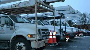 Nearly a dozen bucket trucks from the Massachusetts-based Harlan Electric Company sat ready and waiting Monday night outside of the Desmond hotel in Albany. The company is a contractor for National Grid. Power outages are expected due to high winds. (Keshia Clukey/ Times Union)