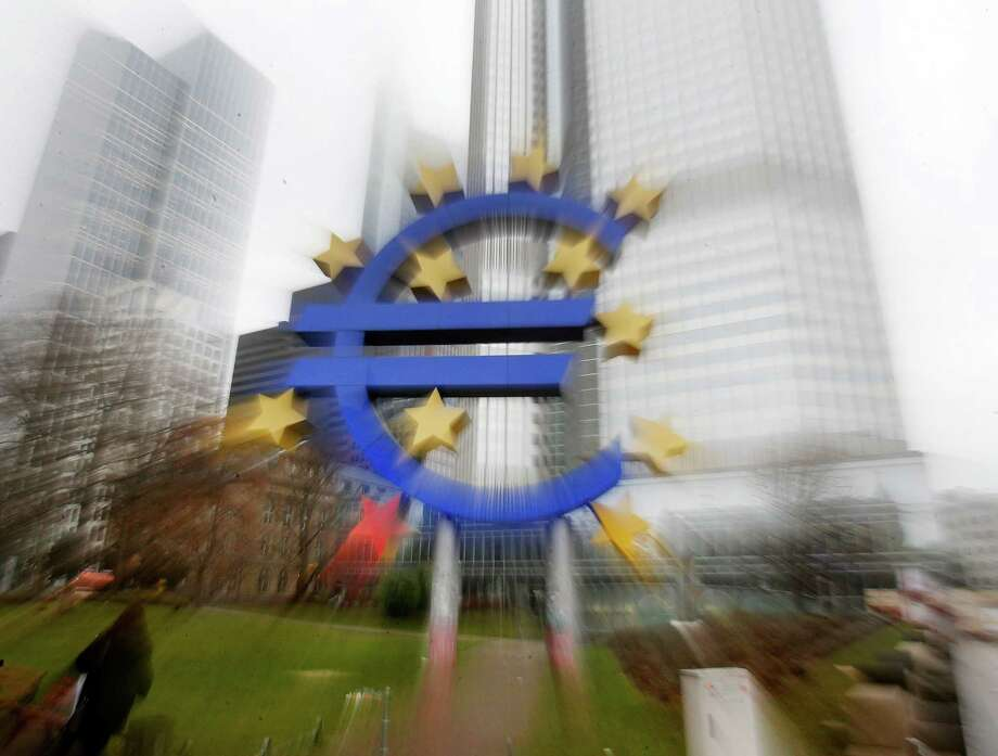 In this zoomed picture the Euro sculpture stands in front of the old European Central Bank in Frankfurt, Germany, Monday, Jan. 26, 2015.  The euro wobbled Monday after Greece's anti-austerity opposition party won a big victory in national elections, renewing fears the European common currency bloc could unravel.(AP Photo/Michael Probst) Photo: Michael Probst, STF / AP