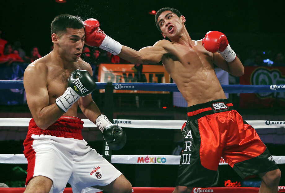 Christian Santibanez (left) is hit by Albert Romero during their lightweight bout. Photo: Edward A. Ornelas /San Antonio Express-News / © 2015 San Antonio Express-News