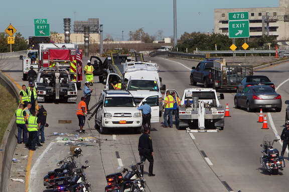 Crews clean up an accident after a truck carrying vehicles overturned on Interstate-45 northbound near West Dallas Street, Monday, Jan. 26, 2015, in Houston. The accident left debris throughout the area, causing lane closures heading northward into downtown.