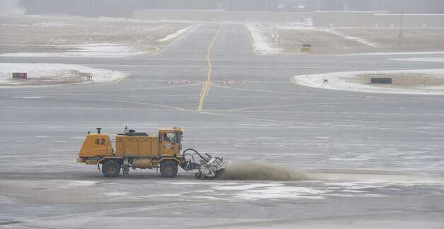 A crew at Albany International Airport clears sand off the tarmac on Tuesday, Jan. 27, 2015. Forecasters predicted up to a foot of snow could fall on the Capital Region but barely a dusty actually fell. (Skip Dickstein / Times Union)