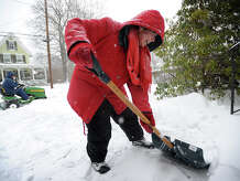 Robbie Silver and her husband Bill clear snow from in front of their Governors Avenue home in Milford, Conn. on Tuesday, January 27, 2015.