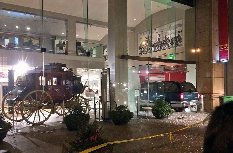 A vehicle is seen smashed into the window of the Wells Fargo History Museum in downtown San Francisco, Tuesday, Jan. 27, 2015. Thieves in the SUV smashed through the glass doors of the museum and made off with gold nuggets on display. (AP Photo/Kristin Bender) Photo: Kristin Bender, Associated Press