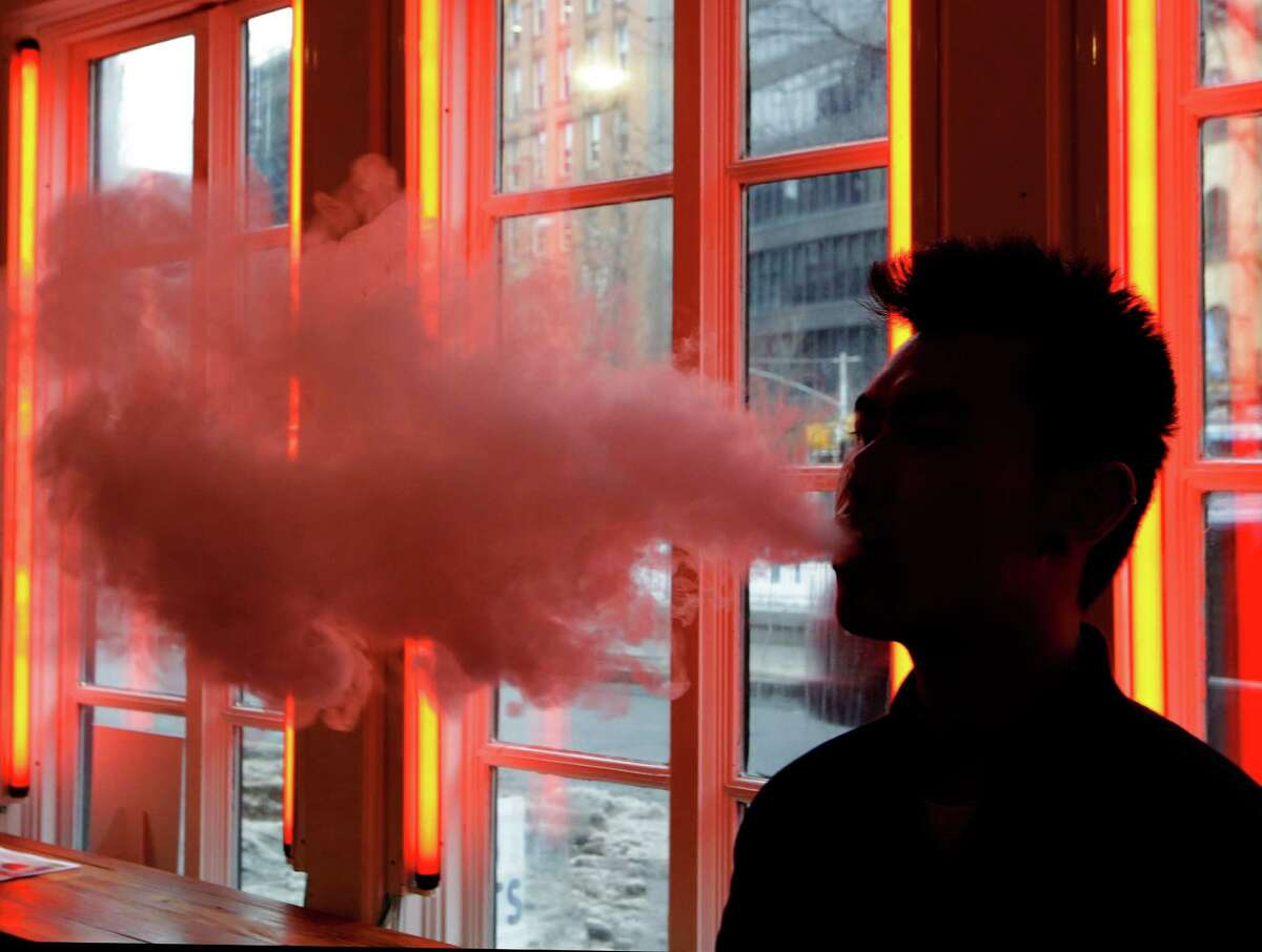 An e-cigarette user exhales vapor. Using certain e-cigarettes at high settings could release much more formaldehyde, a cancer-causing chemical, than smoking traditional cigarettes does, lab tests suggest. The research published in the New England Journal of Medicine on Wednesday, Jan. 21, 2015, is not proof of a risk - it involved limited testing on just one brand of e-cigarettes. But scientists say it shows how little is known about the safety of these popular devices.