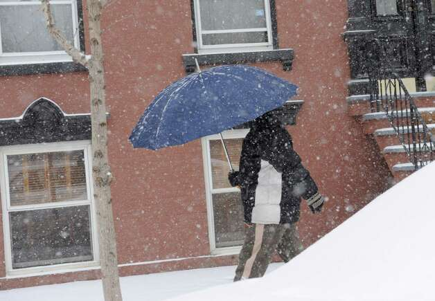 A woman walking down Madison Ave. uses an umbrella during a snow storm on Tuesday, Jan. 27, 2015 in Albany, N.Y. (Lori Van Buren / Times Union) Photo: Lori Van Buren
