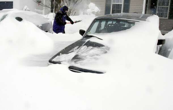 Paul Baxter digs his cars out of drifted snow after a winter storm, Tuesday, Jan. 27, 2015, in Marlborough, Mass. A storm packing blizzard conditions spun up the East Coast early Tuesday, pounding parts of coastal New Jersey northward through Maine with high winds and heavy snow. (AP Photo/Bill Sikes)