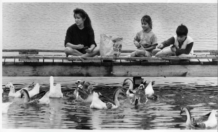 Monica Cardenas, along with her daughter Tiffany Cardenas and son Steven Ramos, feed bread to the ducks and geese after she finishes running around the lake, October 11, 1993.