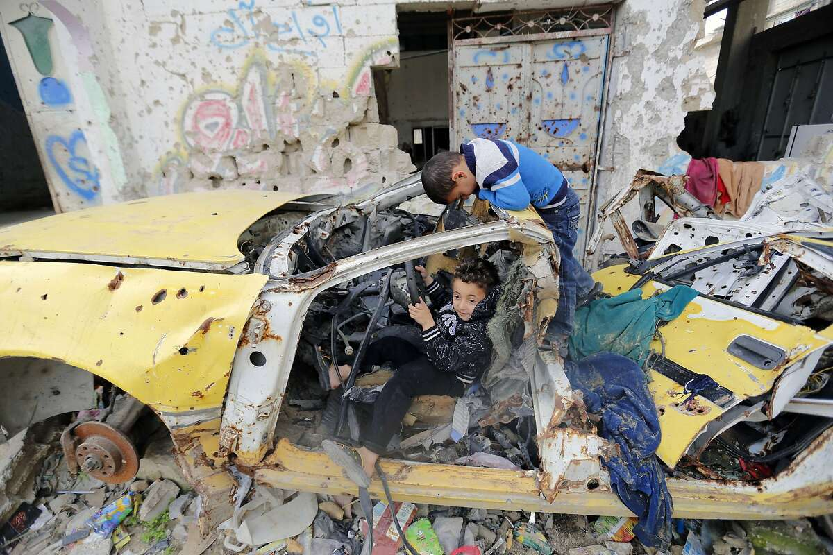 BROKEN PROMISES: In Gaza City, Palestinian boys pretend to drive a car destroyed during last year's 50-day war between Israel and Hamas-led militants. The UN agency for Palestinian refugees said it cannot afford to repair Gaza homes damaged in the war because donors have reneged on promises of funding. Of the $5.4 billion pledged at an aid conference last year in Cairo, virtually none of it has reached Gaza.