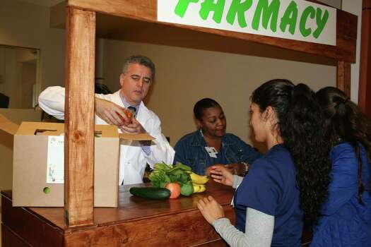 Dr. Garth Davis and Renee Garrett explain what comes in a Farmacy box before presenting Luci Lopez with her prescription order. Photo: Tom Behrens