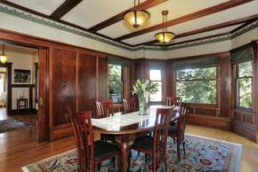 Exposed beams, wood-paneled walls and wallpaper decorates the formal dining room.