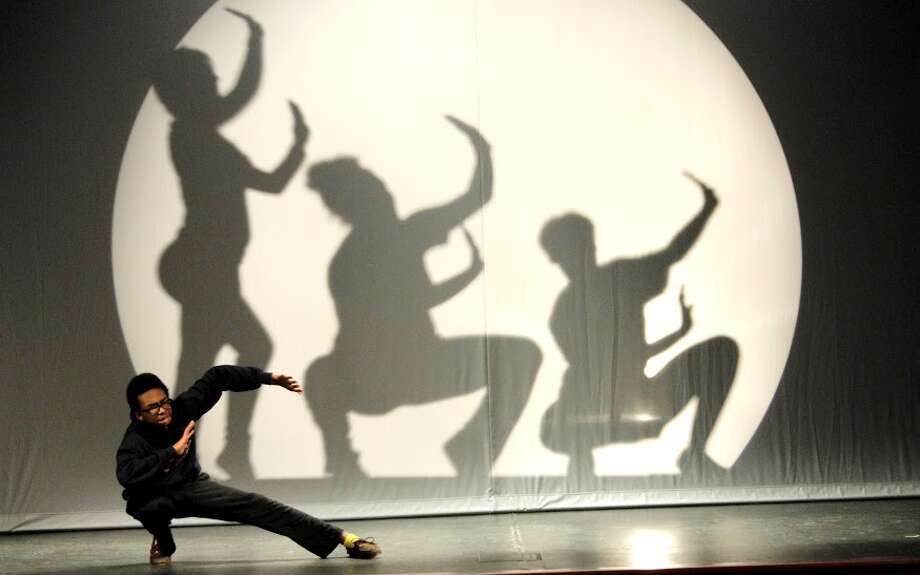 Jamir Brown, left, portrays Seymour in Manvel High School's production of 'Little Shop of Horrors,' which includes dancing  choreographed by senior Hannah Meade. Behind Brown are shadows of dancers Kennedy Haygood, Scarlett Knight and Brianna TenBrink. Photo: Diego Portillo
