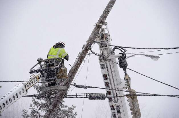 Here  comes the snow ... National Grid and Verizon workers repair a broken utility pole on Route 155 in Loudonville on Tuesday, Jan. 27, 2015.  (Skip Dickstein / Times Union)